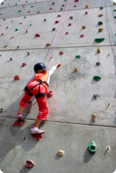 Youngster climbing wall by ccaetano at iStockphoto